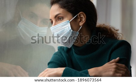 Upset young Caucasian woman in medical facial mask look in window feel lonely distressed sick with covid-19. Unhappy female in facemask suffer from coronavirus. Quarantine, corona pandemic concept.