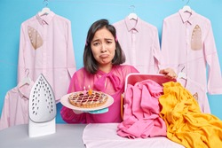 Upset young woman busy doing housework even on her birthday holds baked pie with number burning candles expresses negative emotions stands near ironing board with huge pile of wrinkled laundry