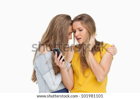 Upset young woman looking her cellphone consoled by her friend against white background - stock photo