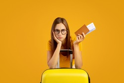 Upset young woman with passport and plane tickets leaning on suitcase, missed her vacation because of COVID-19. Quarantine and travelling concept. Sad lady staying home cause of pandemic