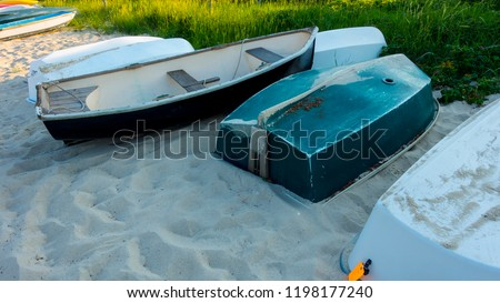 upside down and upside right rowboats with gold sun rays of sunset sunrise on sand not being used