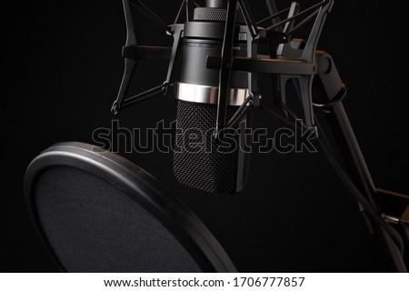 Upside Down Black Condenser Microphone in Shock Mount  with Pop Filter Facing Left Side Stock fotó ©
