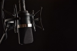 Upside Down Black Condenser Microphone in Shock Mount  with Pop Filter on Left with Negative Space for Type