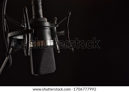 Upside Down Black Condenser Microphone in Shock Mount  with Pop Filter on Left with Negative Space for Type Stock fotó ©