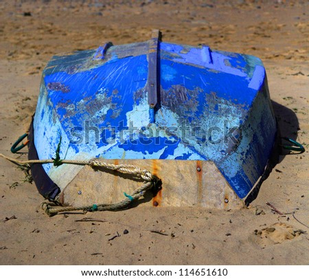 Upside down blue boat on Staithes beach