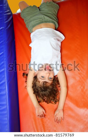 upside down little girl on playground slide laughing happy
