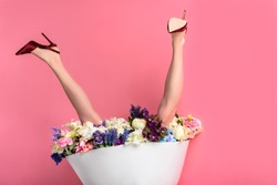 upside down of female legs in high heeled shoes and skirt with beautiful flowers isolated on pink