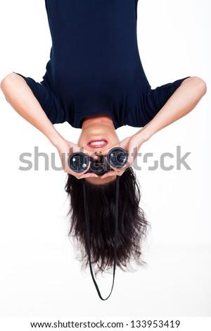 upside down photo of young woman holding binoculars
