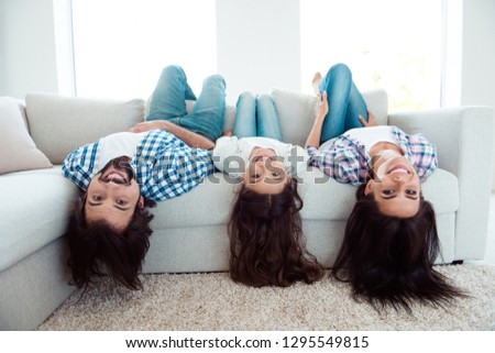 Upside down portrait of nice cute charming attractive cheerful cheery people mom dad lying on divan having fun in light white modern interior indoors #1295549815