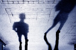 Upside down shadow of two person on pattered sidewalk, in black and white