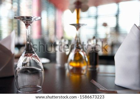 Upside down wine glasses on restaurant table, close-up, surface level, focus on foreground