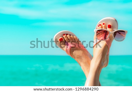 Upside woman feet and red pedicure wear pink sandals, sunglasses at seaside. Funny and happy fashion young woman relax on vacation. Girl on beach. Creative for tour agent. Weekend travel. Summer vibes