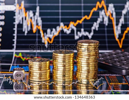 Uptrend stacks coins, dices cube with the word GO and calculator on the financial stock charts as background. Selective focus