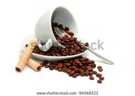 Upturned cup with coffee beans and candy