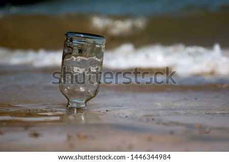 Upturned glass bottle buried in the sand with waves, surf and sand in the background at Diu beach Gujarat India. Shows the place where most of gujarat comes to consume alcohol given gujarat is a dry