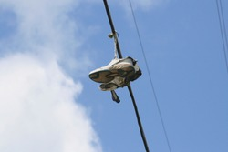 Upward shot of running shoes hanging from electric wires