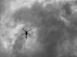Upward View of a Black Helicopter with Dark Gray Clouds Above.