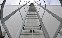 upward view of a fire inspection ladder installed on the wall of a building or on chimneys. has a guide rope for tying the rope of the climber's belt. protective grille galvanized metal gray tunnel