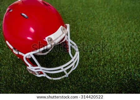 Upward view of an american football helmet on the field