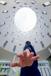 Upward view of an inner courtyard with a man raising his hand in the foreground of a round white building located in Munich Germany