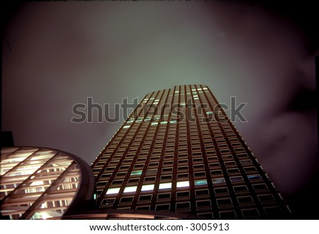 Upward view of several office towers along the skyline in Denver, Colorado at dusk