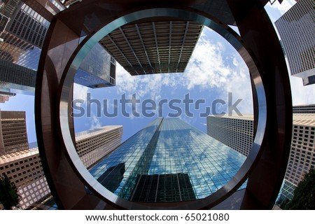 Upward view of tall skyscrapers against a blue sky and clouds in the downtown business area of Houston, Texas.
