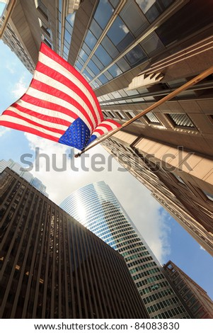 Upward view of tall skyscrapers with the American flag waving in the breeze in the Chicago downtown loop business district.