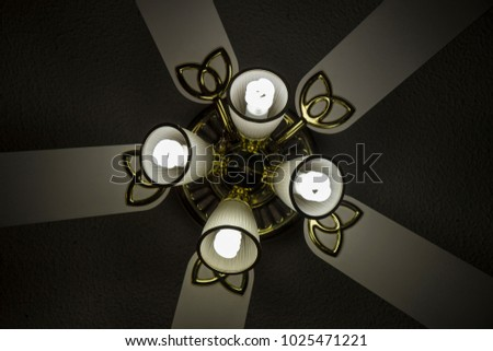 Upward view of white ceiling fan ornate on still object abstract light shadow gold fluorescent