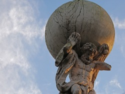 Upwards view to statue of Atlas with blue sky with few clouds in the park