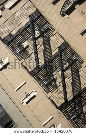Urban apartment traditional metal fire escape at an diagonal angle in sunlight - stock photo