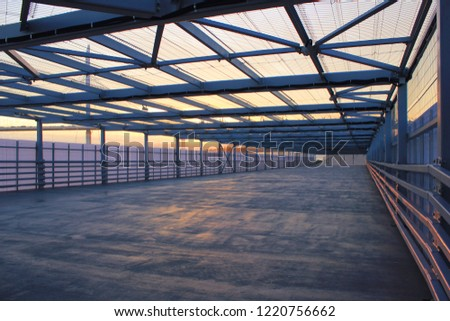 Urban Architecture Abstract Street Passageway Outdoors. Modern Structure of Empty Bridge Road on Evening Sunset Background. Contemporary Urban City Building Interior Passage with Metal Walls and Roof #1220756662