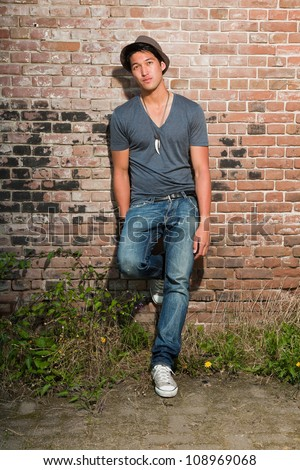 Urban asian man. Good looking. Cool guy. Wearing grey shirt and hat and jeans. Standing in front of brick wall.
