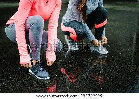 Urban athletes lacing sport footwear for running over asphalt under the rain. Two women getting ready for outdoor training and fitness exercising on cold winter weather.