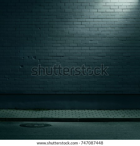 Urban background. Brick wall under the lamp light at night.