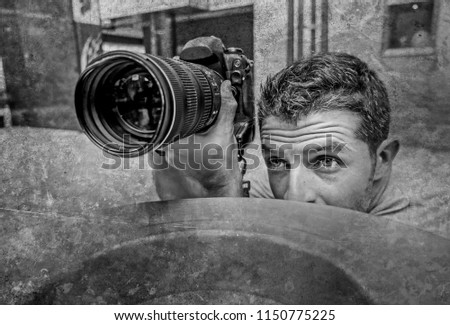 urban background lifestyle funny portrait of young paparazzi photographer man in action hidden behind city paper basket stalking for shooting exclusive photo story on celebrity