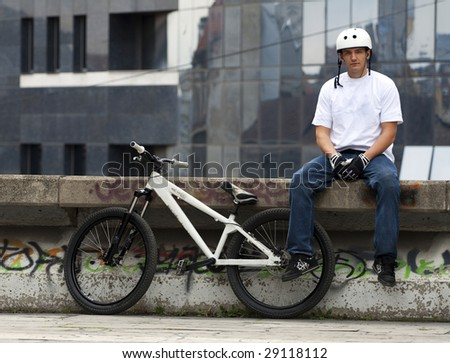 Urban bike rider with modern building in background.