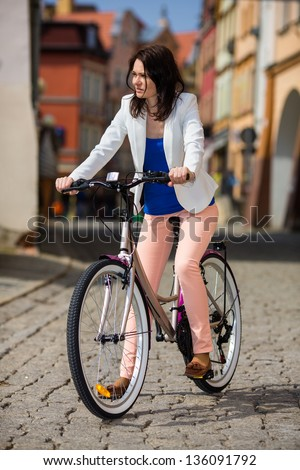 Urban biking -  middle-age woman and bike in city