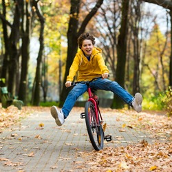 Urban biking - teenage boy riding bike in city park