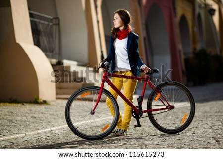 Urban biking - teenage girl and bike in city - stock photo