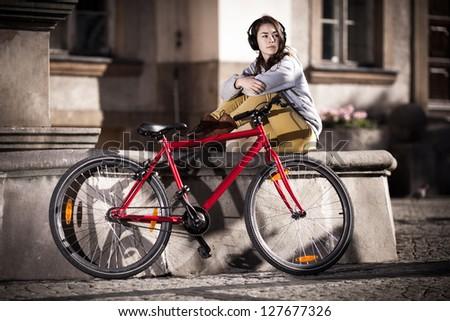 Urban biking - teenage girl and bike in city - stock photo