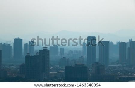 Urban buildings in haze. Environmental pollution in the process of urbanization.