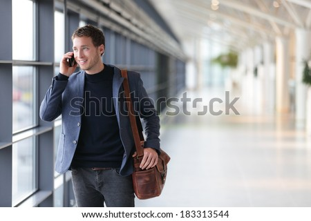 Urban business man talking on smart phone traveling walking inside in airport. Casual young businessman wearing suit jacket and shoulder bag. Handsome male model in his 20s. #183313544