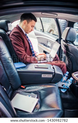 Urban businessman driving in limo while using lap top