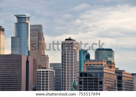 Urban city architecture background.  Group of skyscrapers against cloudy sky close up during sumset. Minneapolis downtown, Minnesota state, Midwest USA.