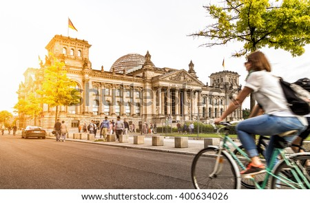 Urban city life with famous Reichstag building in the background in beautiful golden evening light at sunset in summer with retro vintage Instagram style pastel toned filter effect, Berlin, Germany #400634026