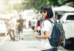 Urban city lifestyle hipster woman wearing summer clothes and trendy sunglasses her eating ice cream walking on downtown street of Bangkok City, Thailand, Concept Travel
