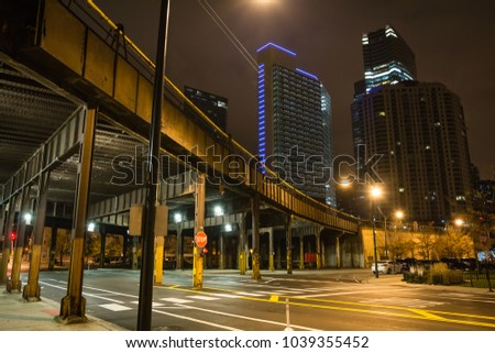 Urban city street corner with vintage train bridge and skyscrapers in Chicago at night #1039355452