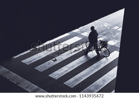 Urban cyclist, unrecognizable man pushing bicycle over pedestrian crosswalk