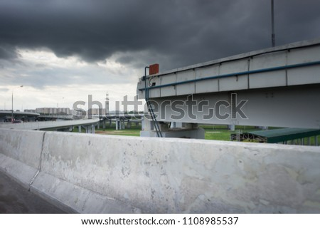 Urban Elevated Roads with concrete blocks on both sides. Black clouds on the sky. Storm is coming #1108985537