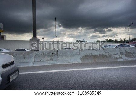 Urban Elevated Roads with concrete blocks on both sides. Black clouds on the sky. Storm is coming #1108985549